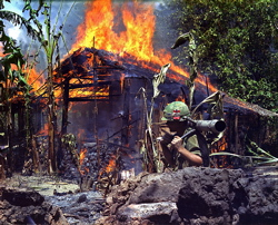 A US soldier watches a wood building burning in the Vietnamese jungle