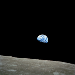 The beautiful blue ball of Earth in the blackness of space, with the surface of the moon below