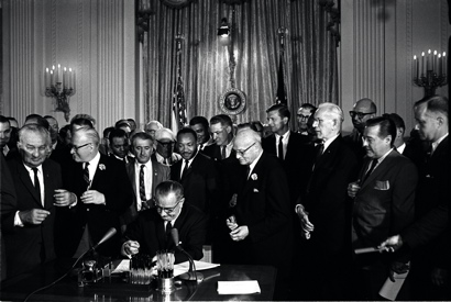 President Johnson signs the Civil Rights Act in 1964 as Martin Luther King and others look on
