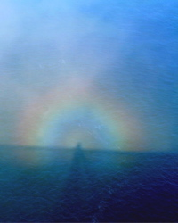 A rainbow halo joins the ocean and the blue sky