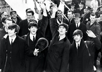 The Beatles wave to their fans after arriving in America in 1964