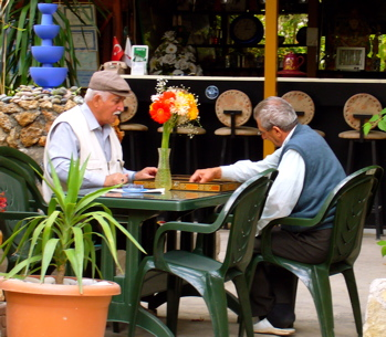 Two older men absorbed in playing backgammon