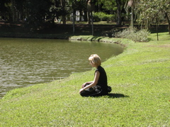 A woman meditates by a lake