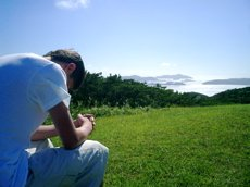 A young man bows his head and prays in the countryside