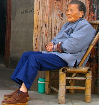 An elderly Asian woman contemplates life – Credit: Phillip Collier