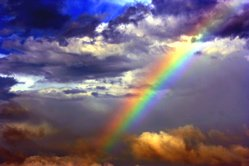 Multi-coloured clouds and a rainbow in the blue sky